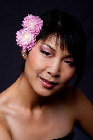 Photo pour Beau visage ombragé d'une femme asiatique-américain avec purple roses fleurs blanches dans les cheveux. - image libre de droit