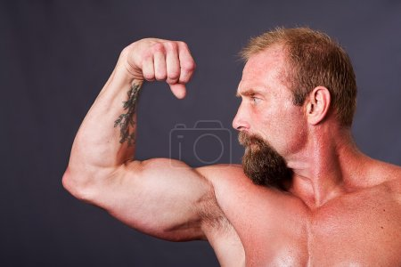 Photo for Middle aged Caucasian strong man with beard looking sideways making a fist to show biceps, isolated. - Royalty Free Image