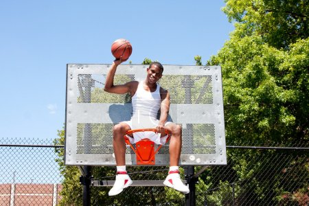 Champion basketball player sits in hoop
