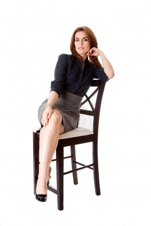 Photo for Beautiful brunette business woman sitting wearing gray skirt and blue blouse with hand on leg with legs crossed, isolated - Royalty Free Image
