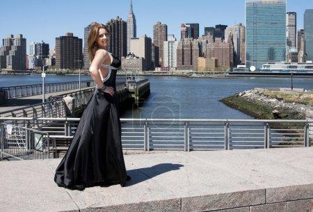 Photo pour Belle heureux souriant caucasien latina fashion modèle femme en robe de cocktail de soirée noir posant debout en face de la ligne d'horizon de manhattan, new york city. - image libre de droit