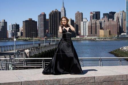 Photo pour Belle heureux caucasien latina fashion modèle femme en robe de cocktail de soirée noir posant debout en face de la ligne d'horizon de manhattan, new york city. - image libre de droit