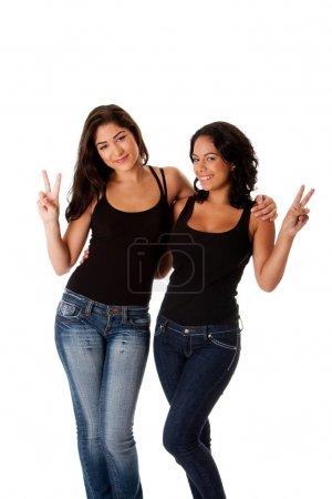 Photo pour Deux belles heureux souriantes jeunes femmes couple amis paix victoire geste avec les doigts tout en étreignant les uns les autres, porter le débardeur noir et bleu denim - image libre de droit