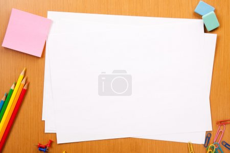 Photo for Set of pencils, erasers, post-its and other useful supplies for the school. There is a centered blank sheet for text writing - Royalty Free Image