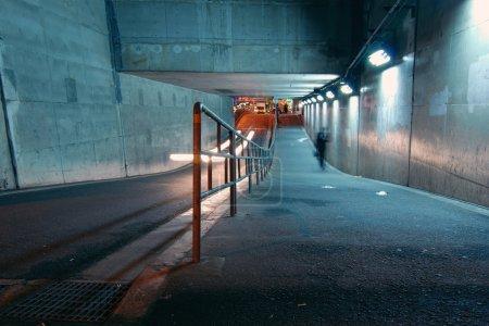 Photo pour Des hommes marchent dans le tunnel en cours à l'obscurité, Osaka, Japon - image libre de droit