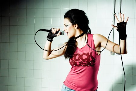 """Photo for Punk Girl singing on an """"underground"""" background high contrast - Royalty Free Image"""