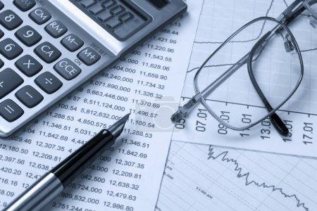 Photo pour Calculatrice, lunettes, couché sur des instruments financiers - image libre de droit