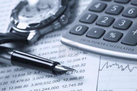 Photo pour Une calculatrice, une horloge et un stylo au-dessus des rapports financiers . - image libre de droit