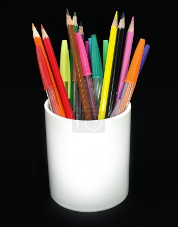 Photo for Colored pencils and pens in a jar against a black background - Royalty Free Image