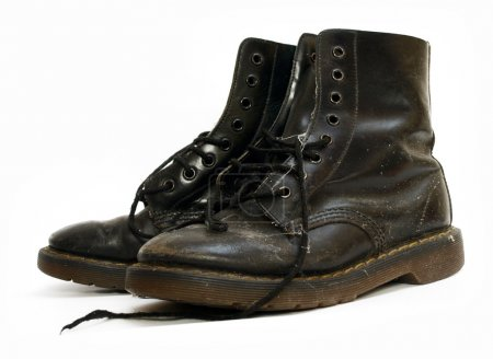 A pair of old black worn out work boots