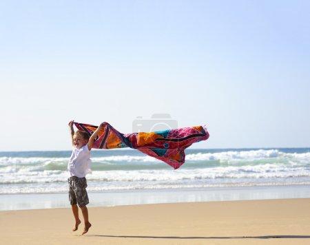 Photo pour Jeune garçon aux cheveux blonds avec un sarong sur la plage - image libre de droit