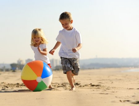 Photo for Beautiful brother and sister play with a beach ball outdoors - Royalty Free Image