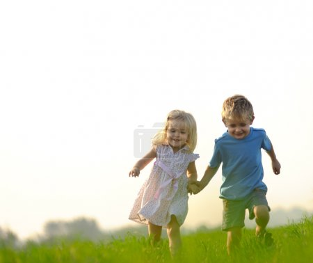 Photo for Brother and sister playing together in a field - Royalty Free Image