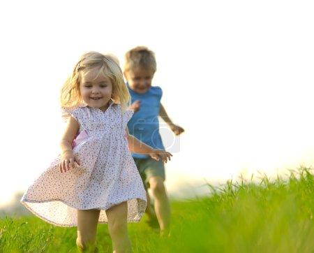 Photo pour Jeune fille court à travers un champ, heureux et s'amuser . - image libre de droit