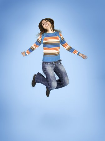 Photo for Beautiful woman jumping over a blue - Royalty Free Image