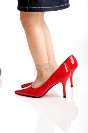 Photo pour Petit enfant jouant whit maman rouge chaussures - image libre de droit