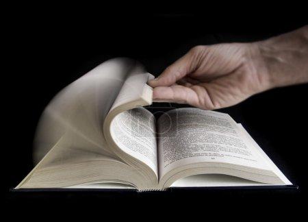 Photo pour Homme main défolier un livre - image libre de droit