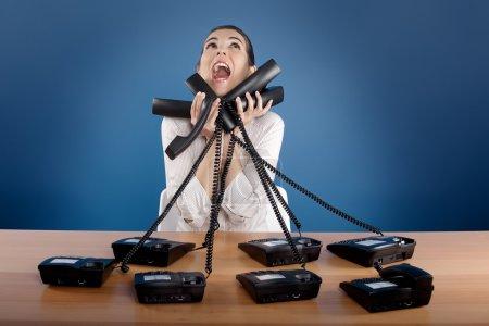 Foto de Empresaria responder un montón de llamadas al mismo tiempo - Imagen libre de derechos