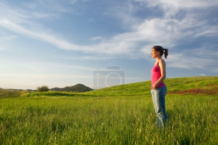 Photo for Beautiful young woman alone on a green field - Royalty Free Image