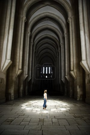 Photo for Woman visiting the big majestic church, with a magic light over her - Royalty Free Image