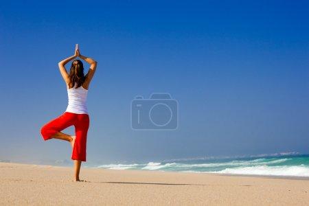 Photo pour Belle jeune femme faisant des exercices de yoga sur la plage - image libre de droit