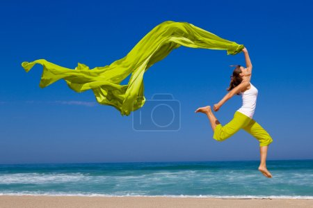 Photo for Beautiful young woman jumping on the beach with a colored tissue - Royalty Free Image
