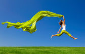 Woman jumping on a green meadow with a colored tissue
