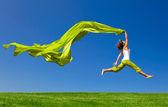 """Постер, картина, фотообои """"Женщина прыгает на зеленый луг с цветной ткани"""""""