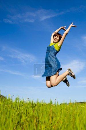 Photo pour Heureuse jeune femme sautant et profitant du printemps par une belle journée - image libre de droit