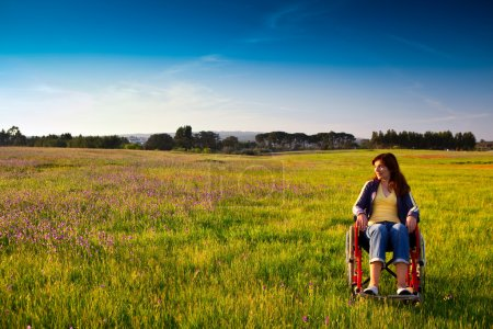 Photo for Happy handicapped woman on a wheelchair over a green meadow looking away - Royalty Free Image