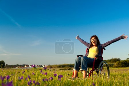 Photo for Happy handicapped woman on a wheelchair over a green meadow - Royalty Free Image