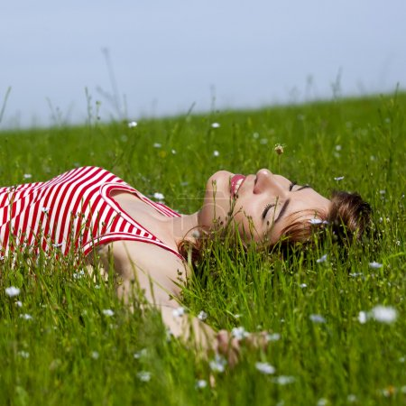 Photo for Young woman relaxing on a beautiful green meadow - Royalty Free Image