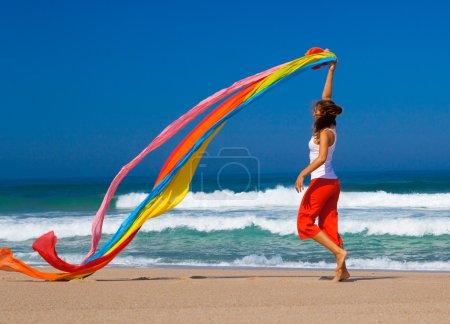 Photo pour Belle jeune femme courant sur la plage avec un tissu coloré - image libre de droit