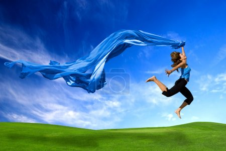 Photo for Beautiful athletic woman jumping on a green meadow with a scarf - Royalty Free Image