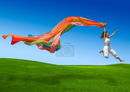 Young beautiful woman jumping with a scarf...