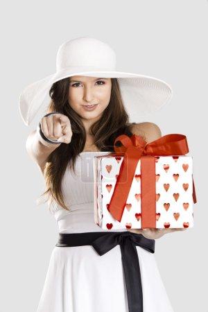 Photo pour Belle et heureuse jeune femme tenant un cadeau et vous montrant du doigt - image libre de droit