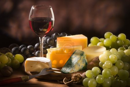 Photo for Glass of red wine with various types of cheese and garnishes - Royalty Free Image