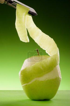 Photo pour Partiellement décortiquée pomme verte à bord vert isolé sur fond vert graduée - image libre de droit