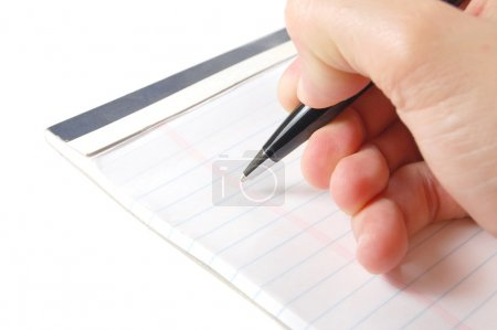 Photo for Macro shot of a hand holding a pen ready to take notes - Royalty Free Image