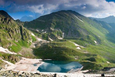 Photo pour Paysage de sommets montagneux avec rivière cristalline, herbe verte, neige et soleil sombre . - image libre de droit
