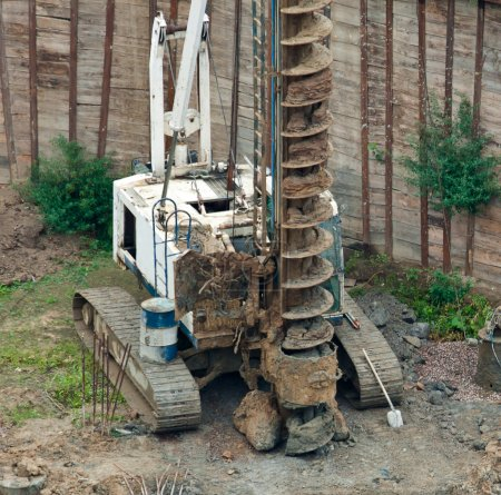 Drilling tractor bores earth on building place....