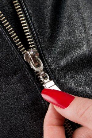 Photo pour Gros plan d'une fermeture éclair et des doigts féminins - image libre de droit