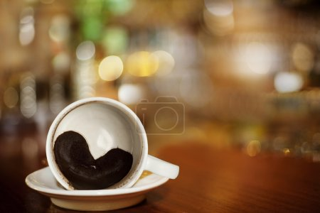 Cup of coffee with Heart of Coffee Grounds on Bar
