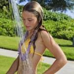 Beautiful teenager in yellow bikini wearing a flow...