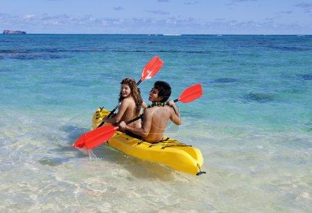 Couple in hawaii paddling a kayak