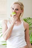 Mladá krásná žena jíst zelené jablko