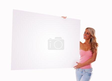 Photo pour Sexy jeune fille tenant un panneau d'affichage ajouter isolé sur fond blanc - image libre de droit