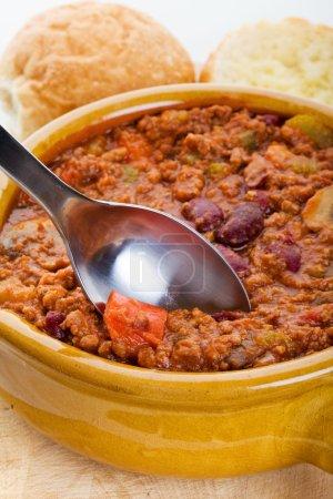 Foto de Tazón de chili con pan crujiente y cuchara - Imagen libre de derechos
