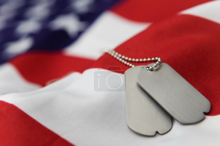 Blank dog tags on American flag with focus on tags...
