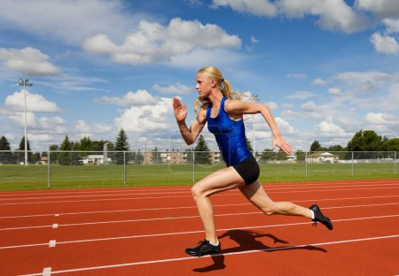 Photo for A female track star sprinting down the race track - Royalty Free Image
